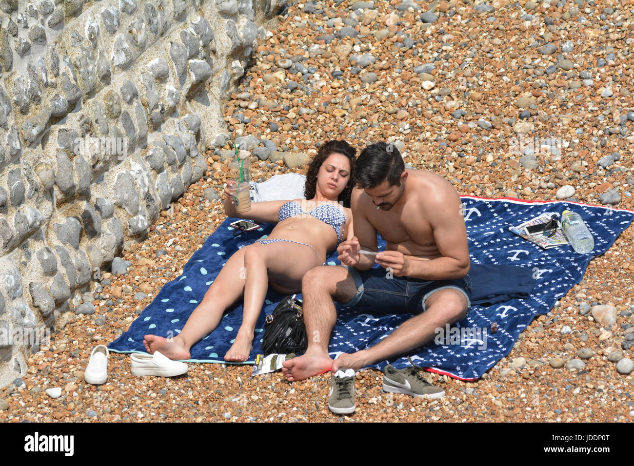 A couple sunbathing in a secluded area of a beach with the man using a mobile phone and woman looking on, in Summer - Stock Image