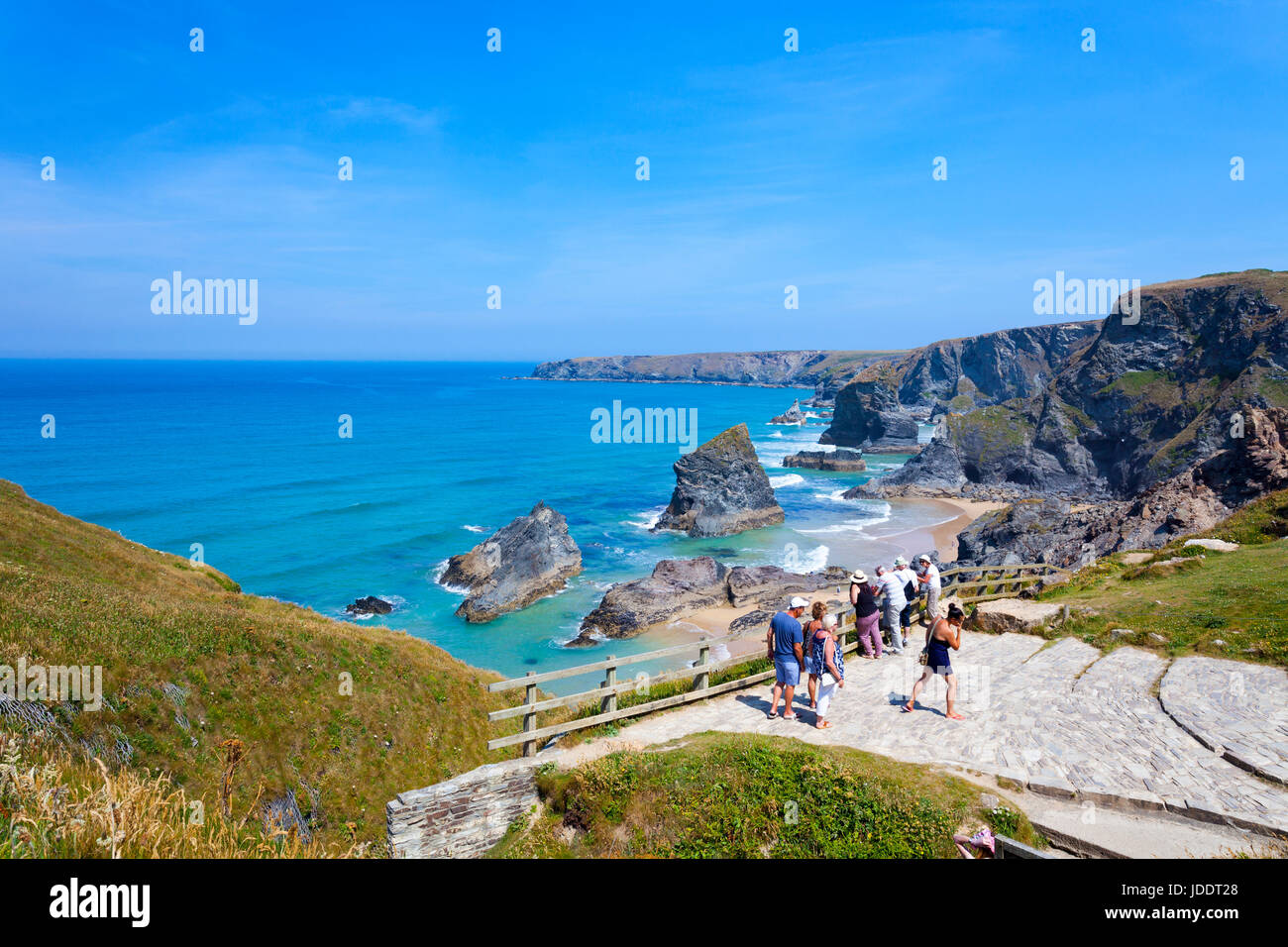 People visiting the popular viewpoint overlooking the beach surf and cliffs at Bedruthan Steps in Cornwall part - Stock Image