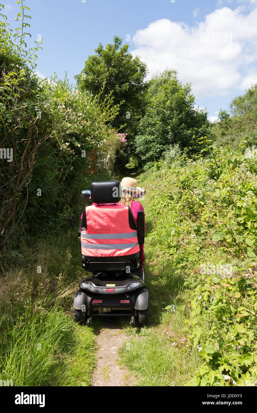 A woman riding a mobility scooter on a country path, giving  disabled access to the countryside, Kent, England UK - Stock Image