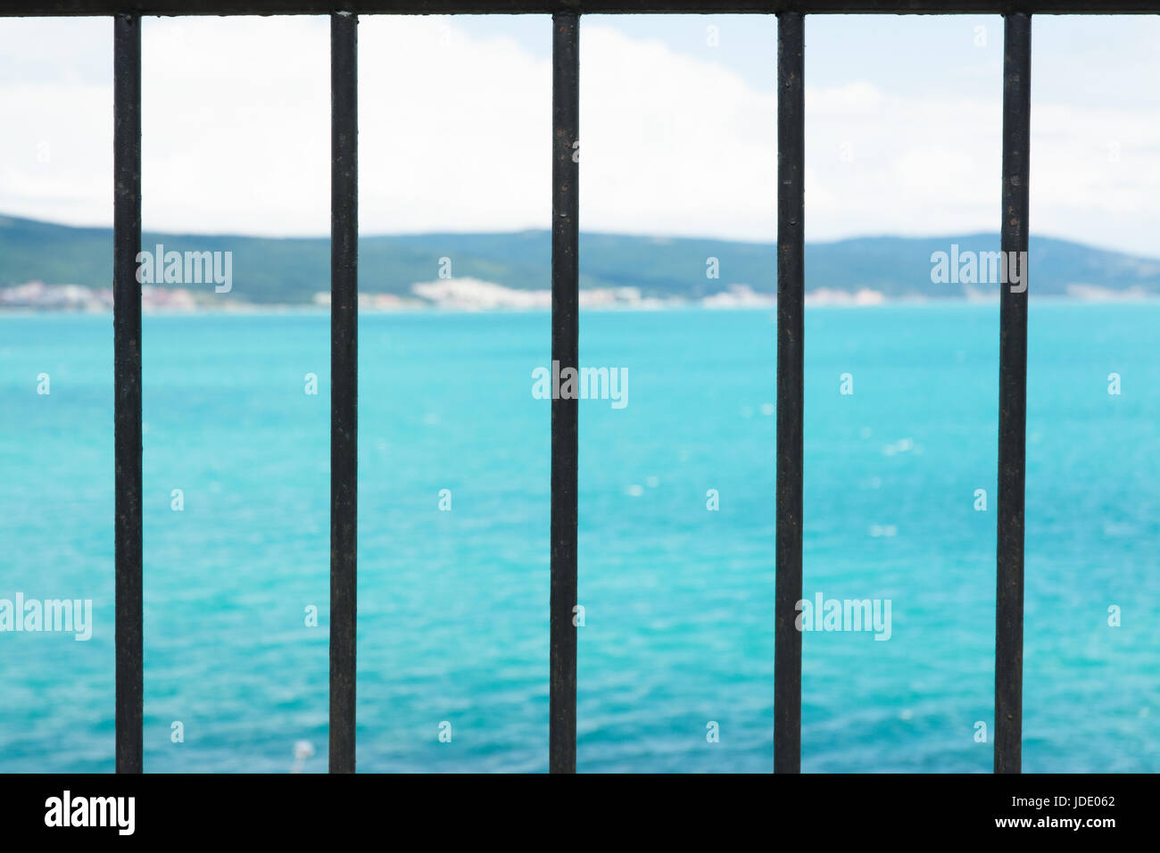 High view on the sea through the metal grate - Stock Image