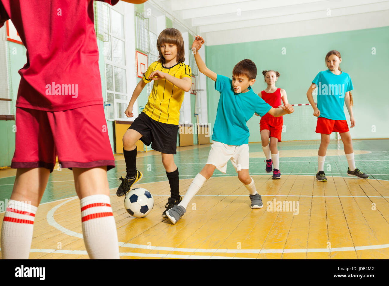 Portrait of preteen boys and girls playing football in school gymnasium - Stock Image