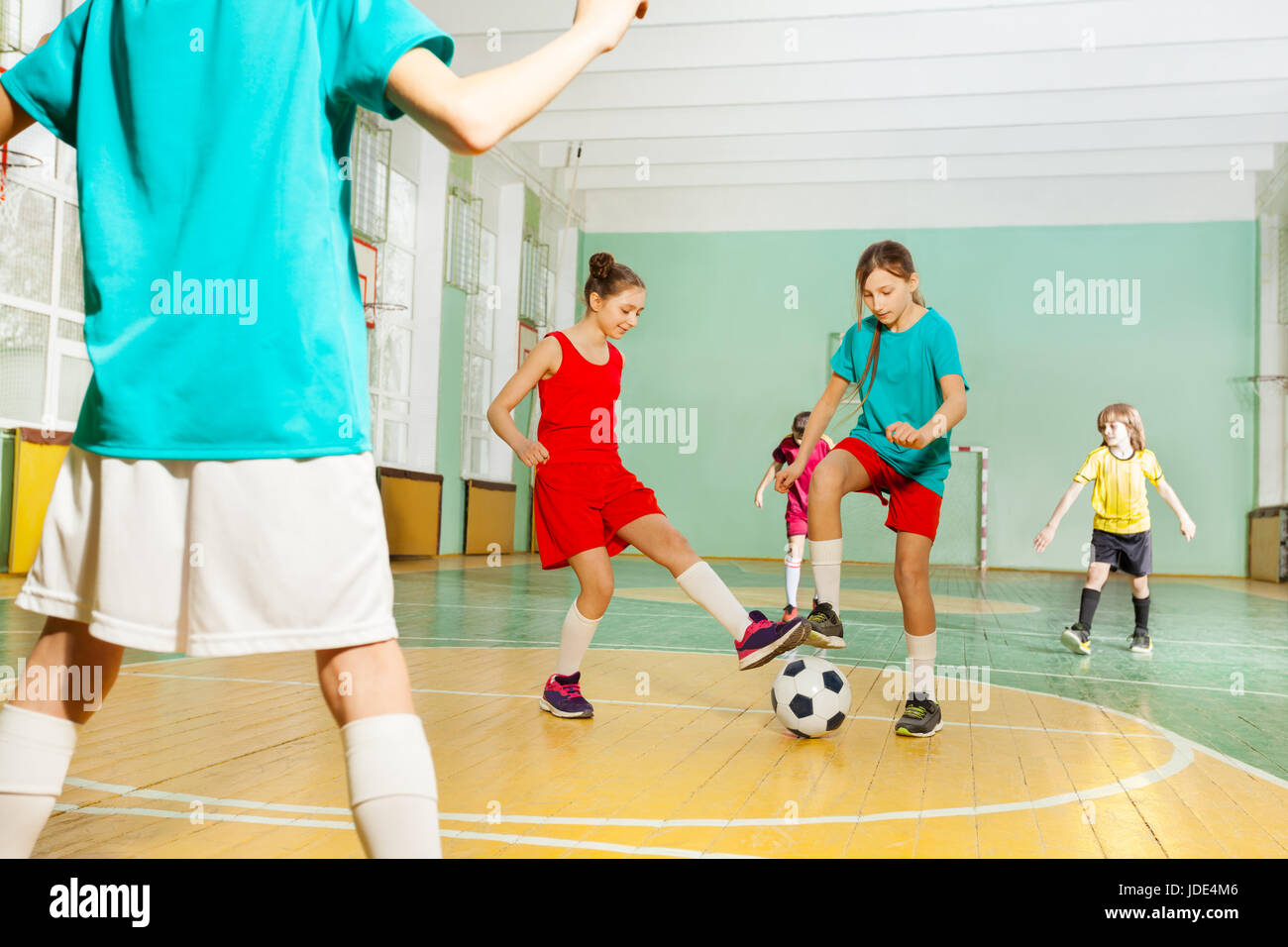 Portrait of preteen boys and girls training football in school sports hall - Stock Image