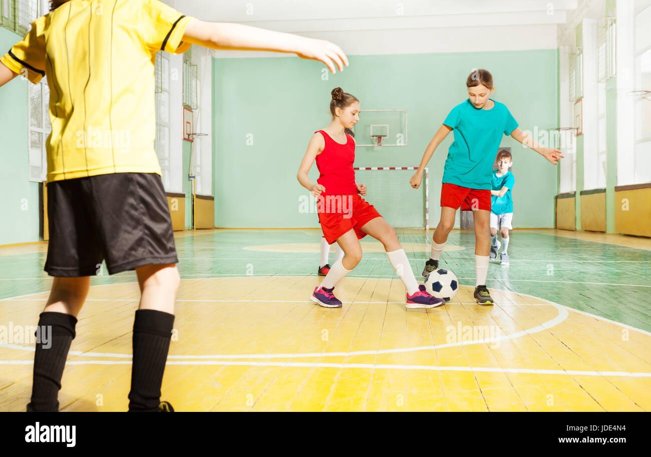 Portrait of preteen boys and girls training football in school gymnasium - Stock Image