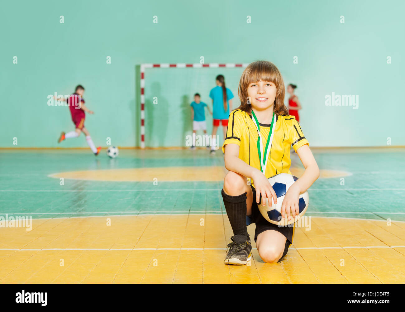 Portrait of smiling preteen boy, soccer team captain, standing on knee in futsal with ball - Stock Image