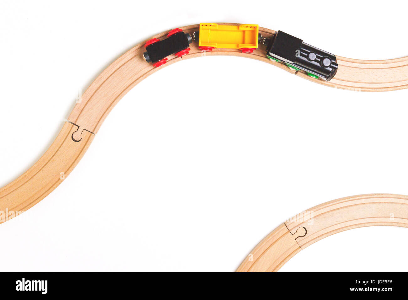 Toy train and wooden rails on white background. Top view. - Stock Image