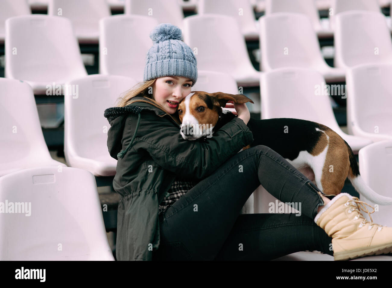 Young hipster girl with her pet estonian hound dog playing and having fun outdoor in the park. Fans at the stadium Stock Photo