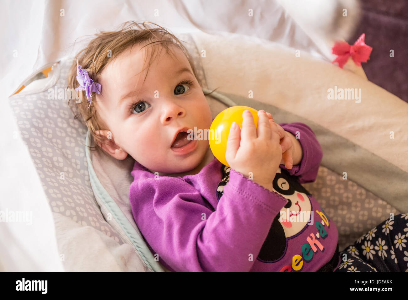 Six month old baby girl playing with a yellow plastic ball in her swing - Stock Image