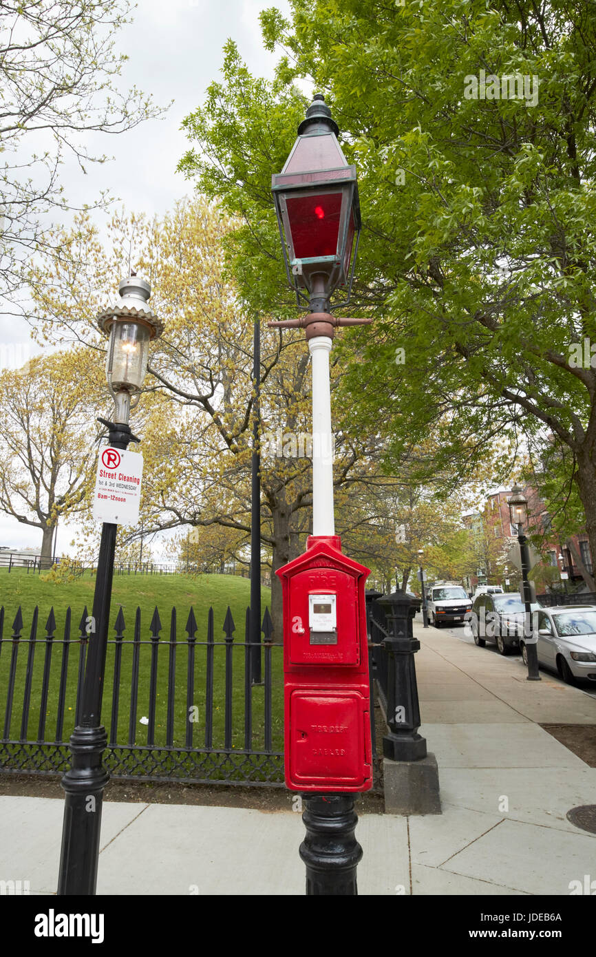 red fire alarm call box and old red tinted gas street light downtown Boston USA - Stock Image