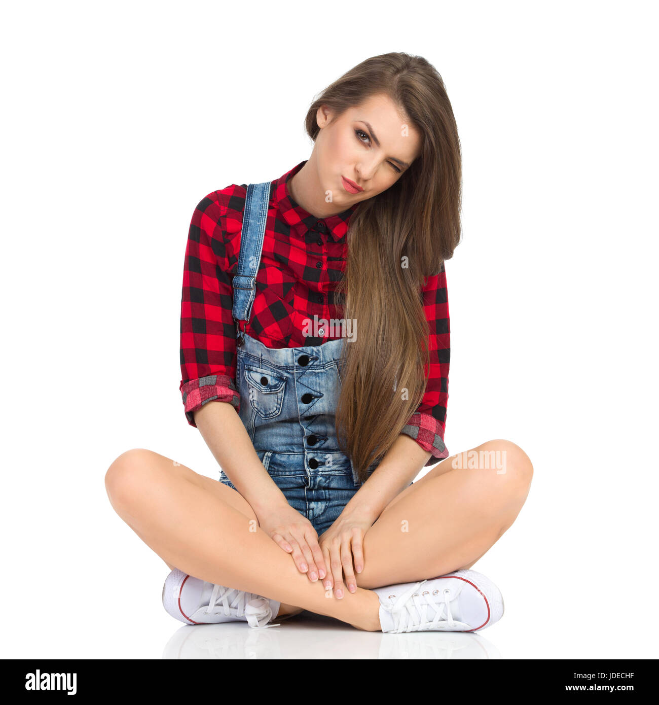 Young woman in red lumberjack shirt, jeans shorts and white sneakers sitting on a floor with legs crossed, looking - Stock Image