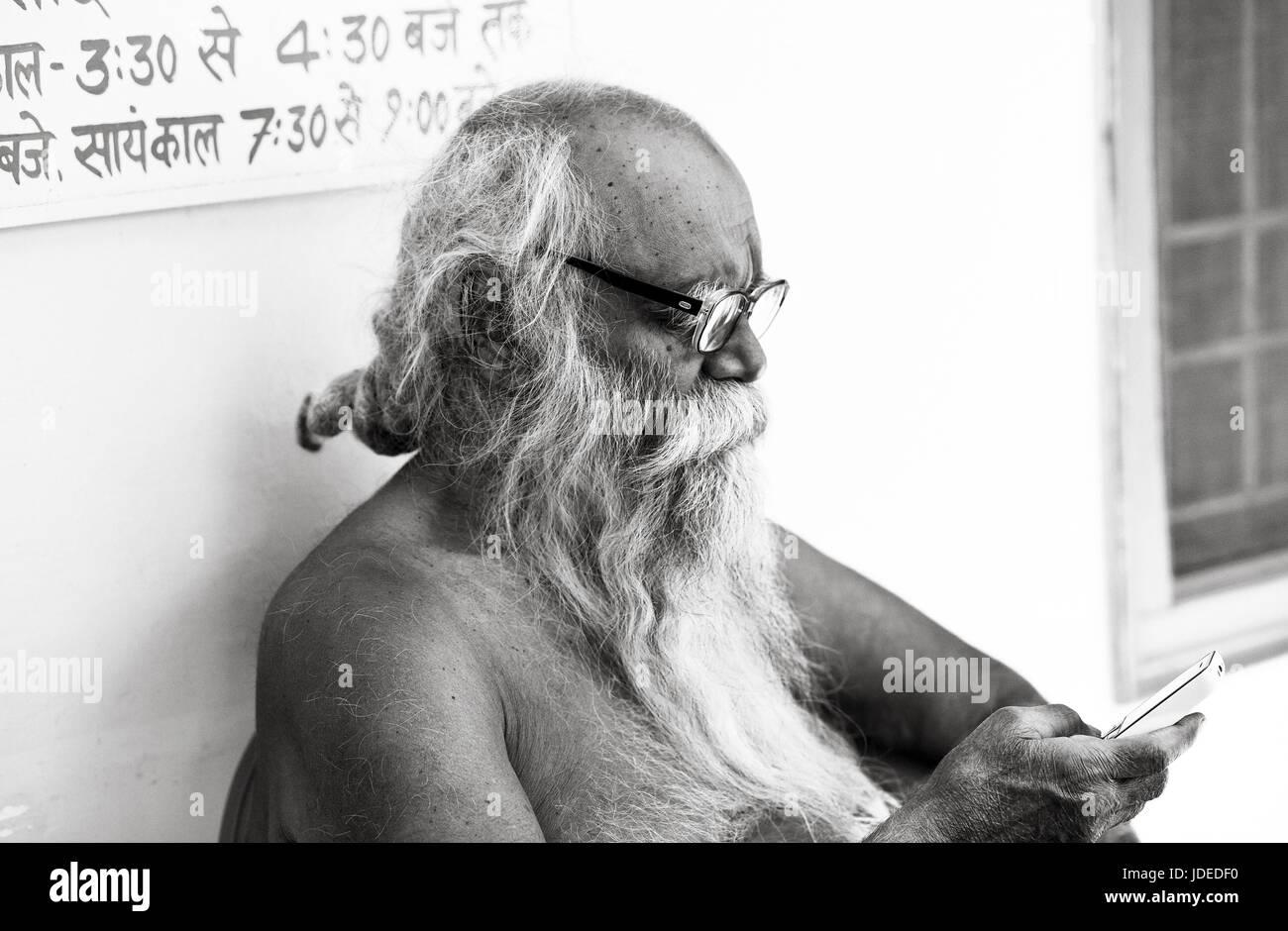 Hindu sadhu checking his phone - Stock Image