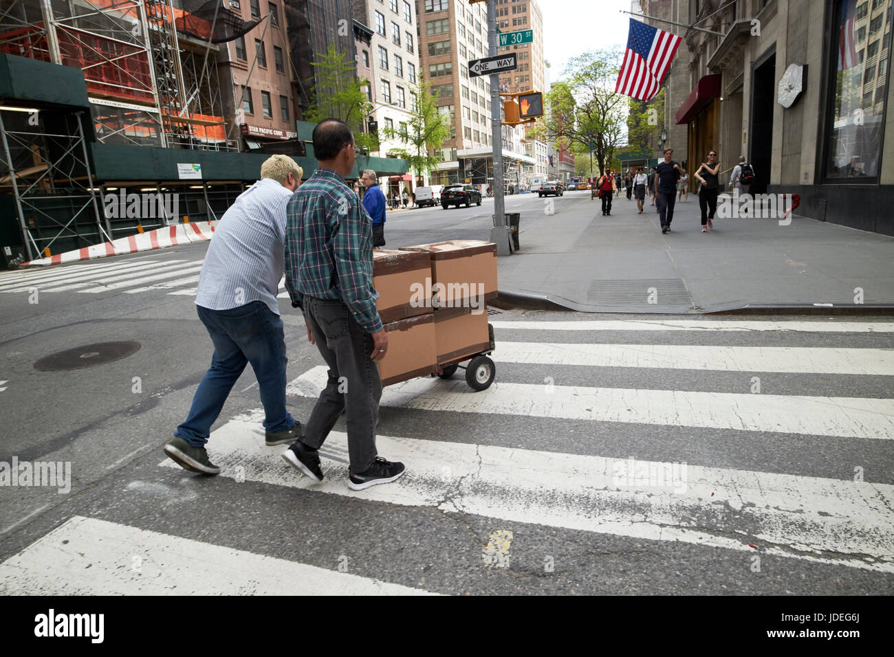 men pushing delivery cart across crosswalk in downtown midtown New York City USA - Stock Image