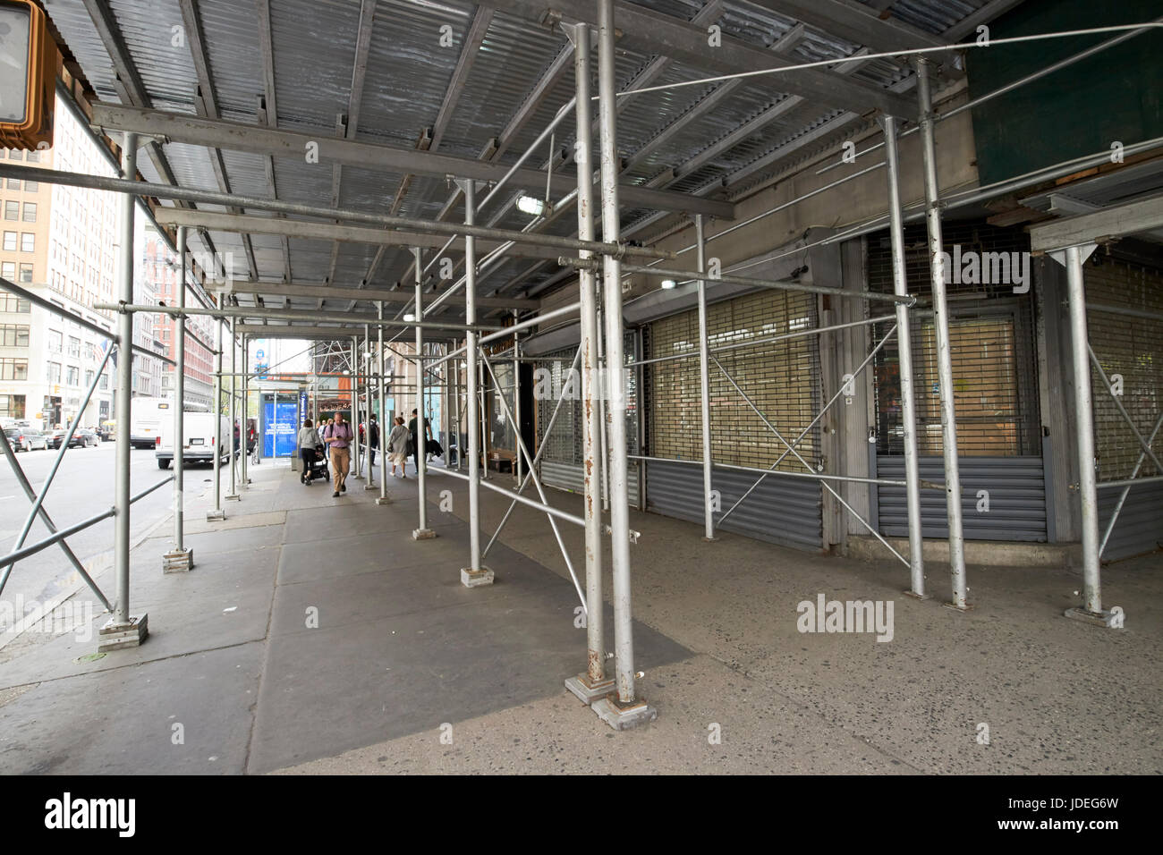 scaffolding over sidewalk next to a building undergoing refurbishment New York City USA - Stock Image