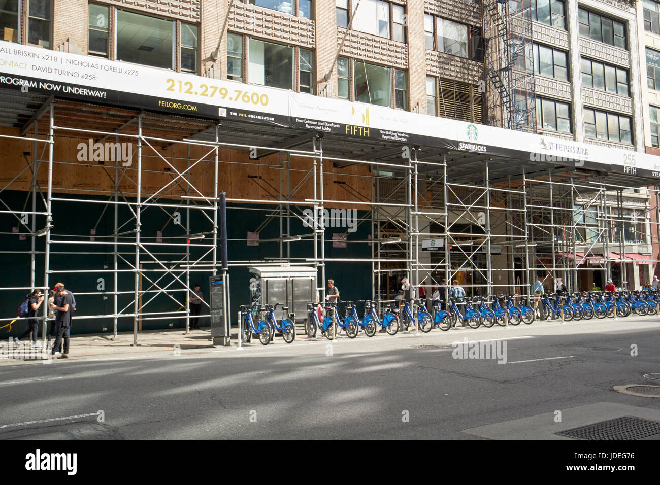 scaffolding over sidewalk and cycle hire station New York City USA - Stock Image
