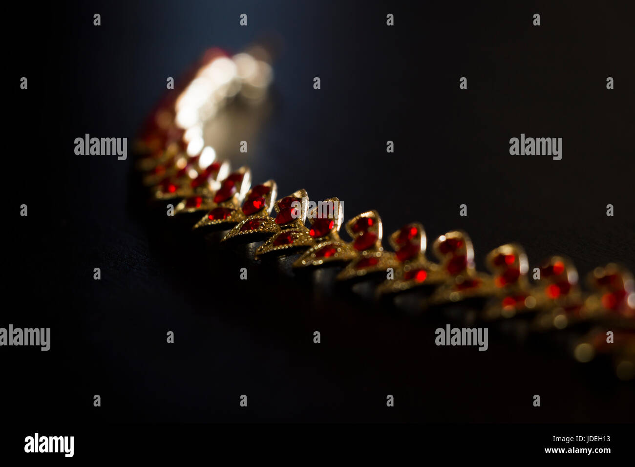 Gold necklace with red stones close-up on a black background Stock Photo