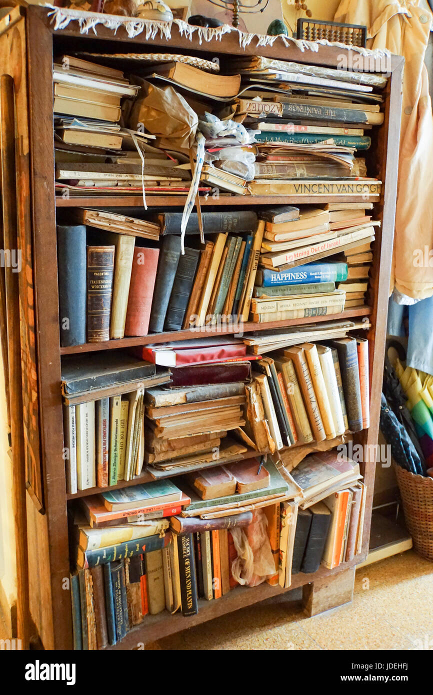 Bookshelf stuffed with old books - Stock Image