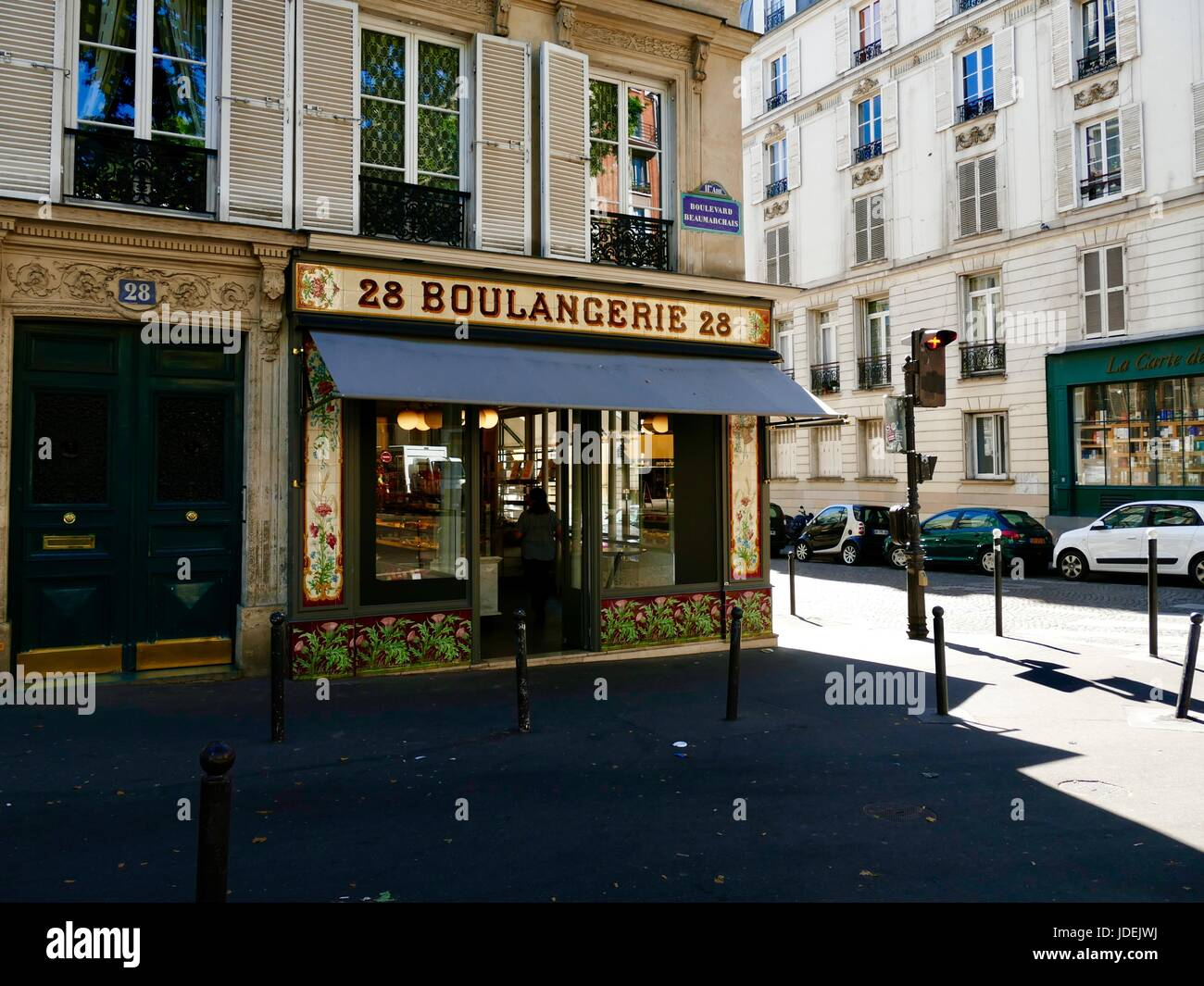 La Boulangerie Beaumarchais, from front, in shadow with side street in sunlight, during June heat wave. Paris, France. - Stock Image
