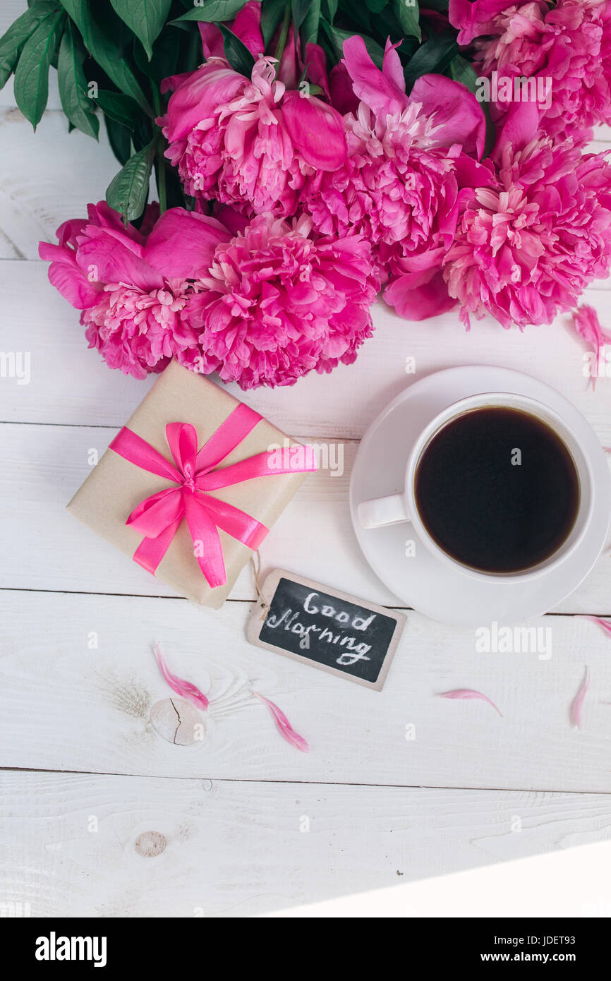 Pink peony flowers,gift box , cup of coffee and notes good morning on white rustic table from above, breakfast on - Stock Image