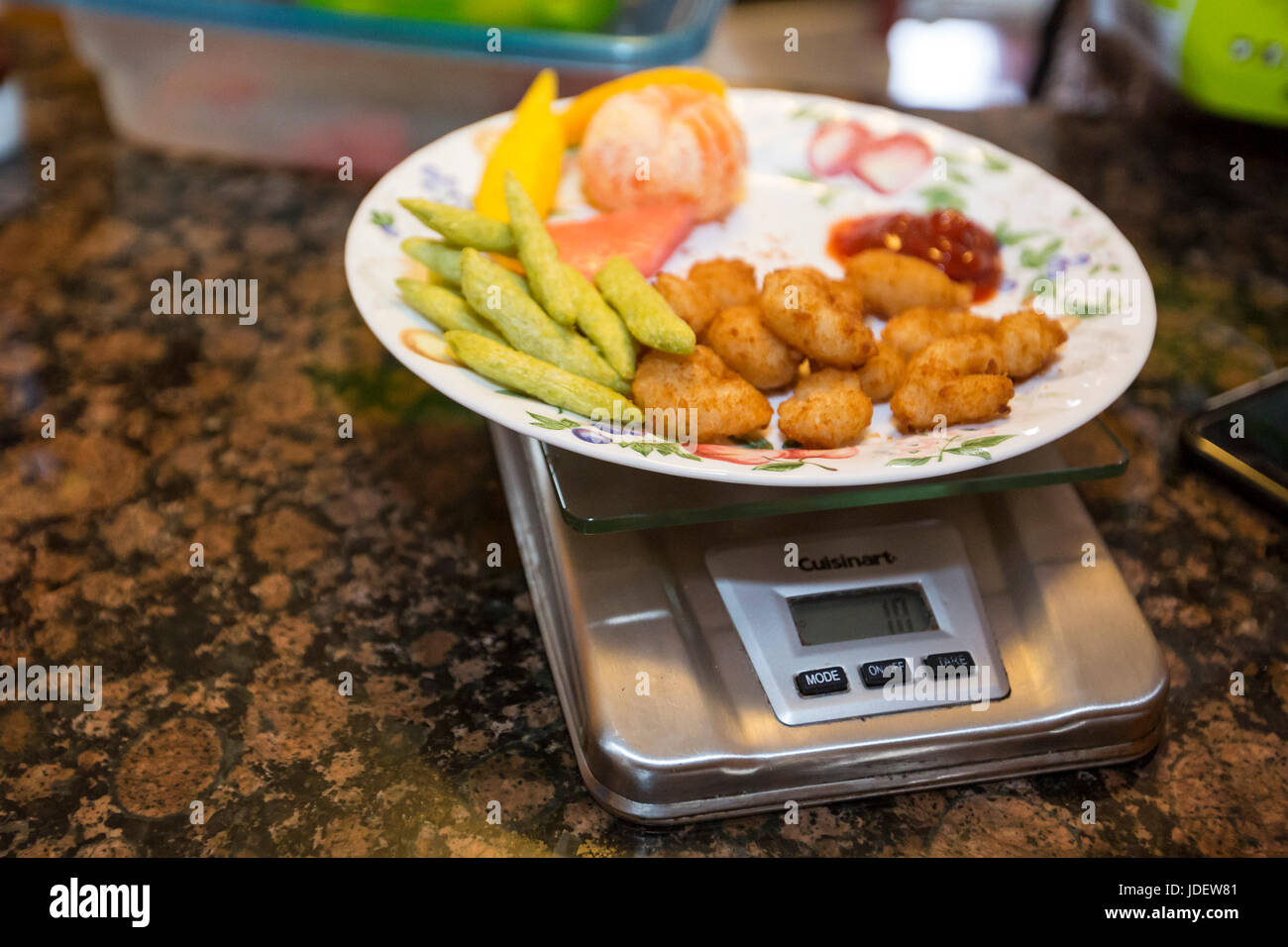 A meal is weighed for a six-year-old boy with type 1 diabetes, also called juvenile diabetes. His diet must be carefully - Stock Image