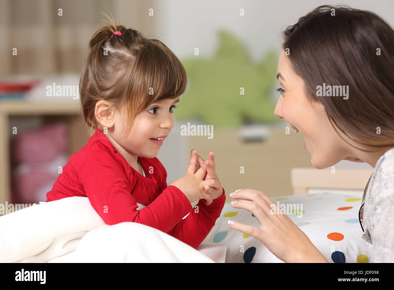 Mother and toddler wearing red shirt playing together on a bed in the bedroom at home - Stock Image