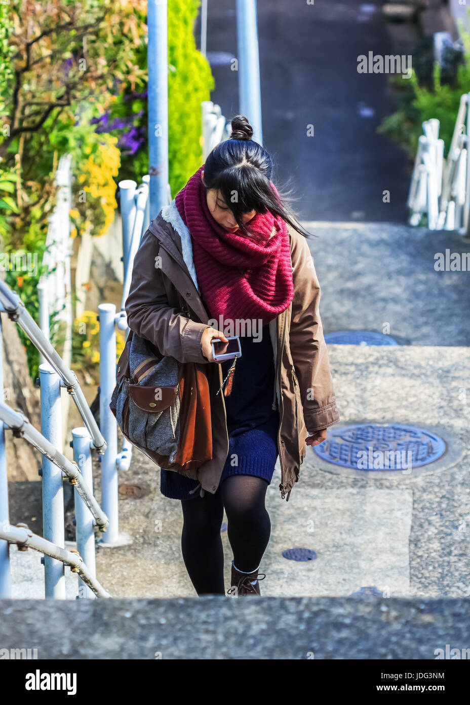 . Unidentified woman uses text chat on the phone while walking upstair - Stock Image