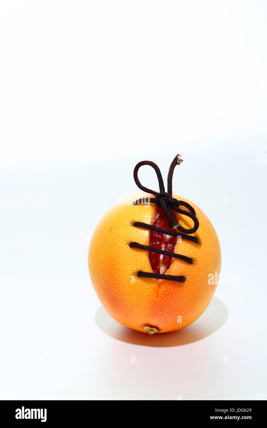 Orange colored fruit with a cut in it and the cut is tied closed with a brown shoe lace on a white background with - Stock Image