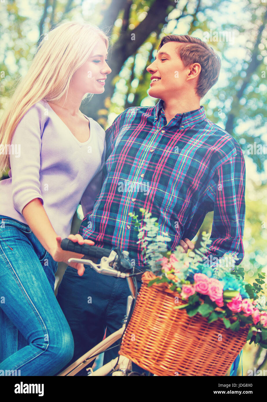 Walking bike of couple in park and kissing. Summer friends walk outdoor. First date of two young people in good - Stock Image