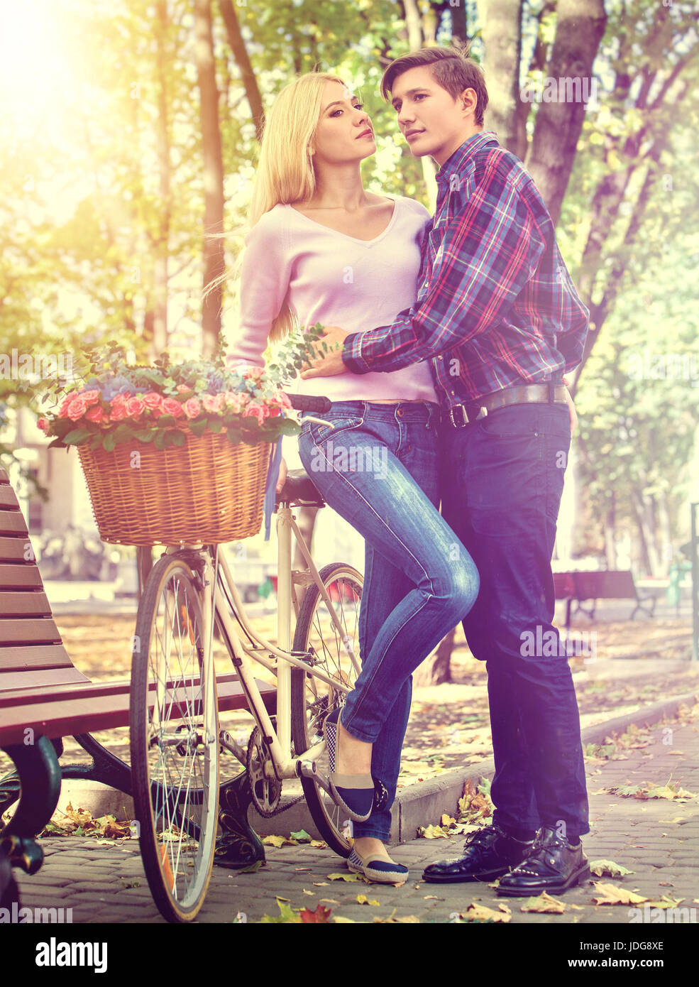 Kissing and walking couple with bike of in park . Summer friends walk outdoor. First date of two young people in - Stock Image
