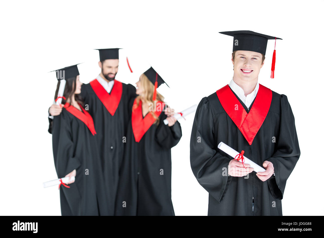 Young student in graduation cap with diploma and friends standing behind isolated on white - Stock Image