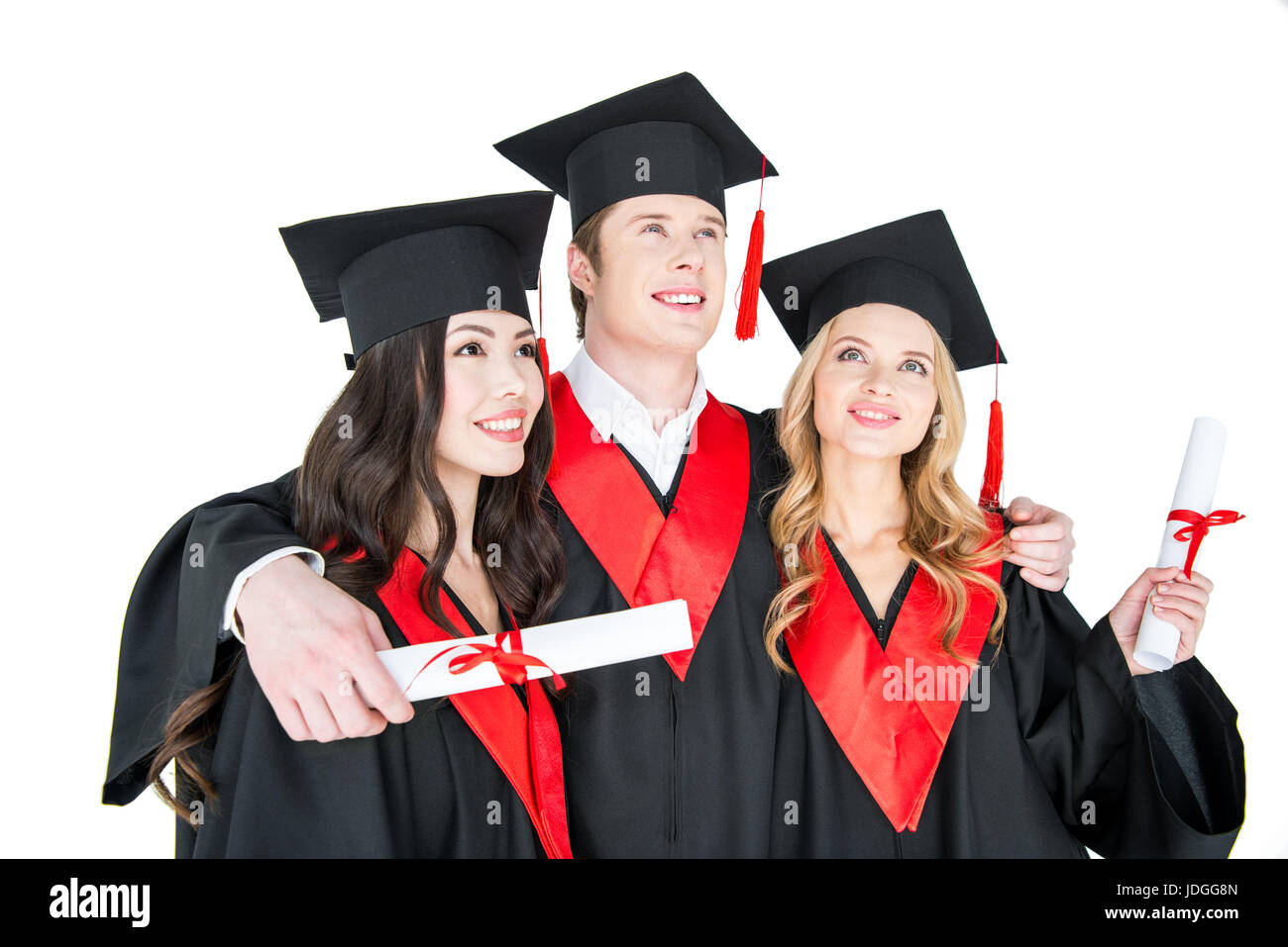 Happy students in academic caps standing embracing with diplomas - Stock Image