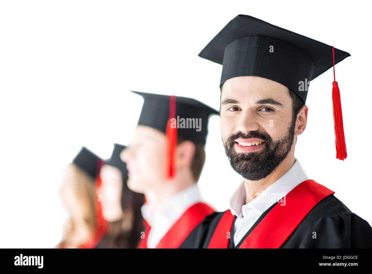 bearded student in graduation cap with diploma, with friends behind isolated on white - Stock Image