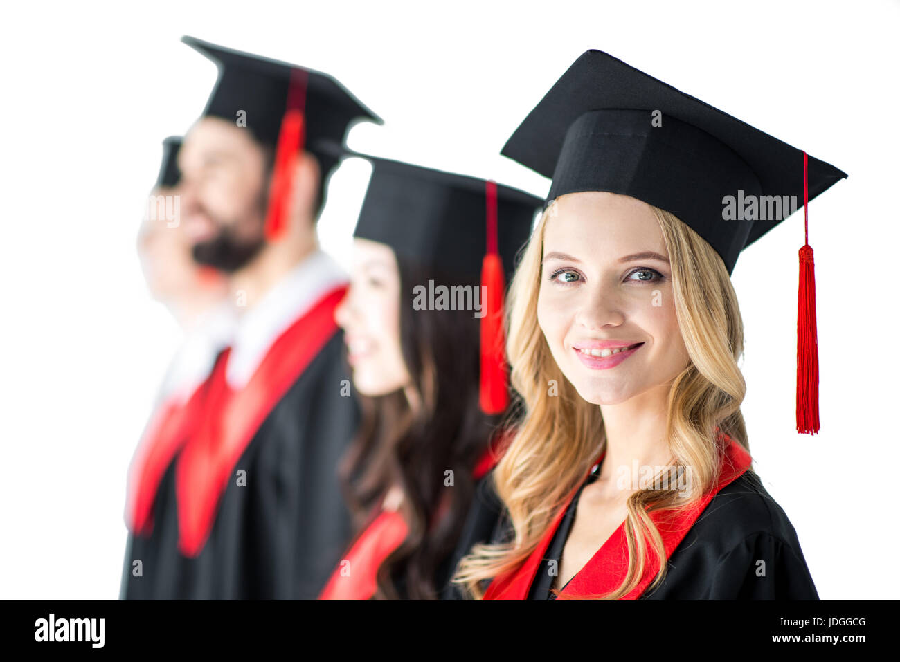 attractive student in graduation cap with diploma, with friends behind isolated on white - Stock Image