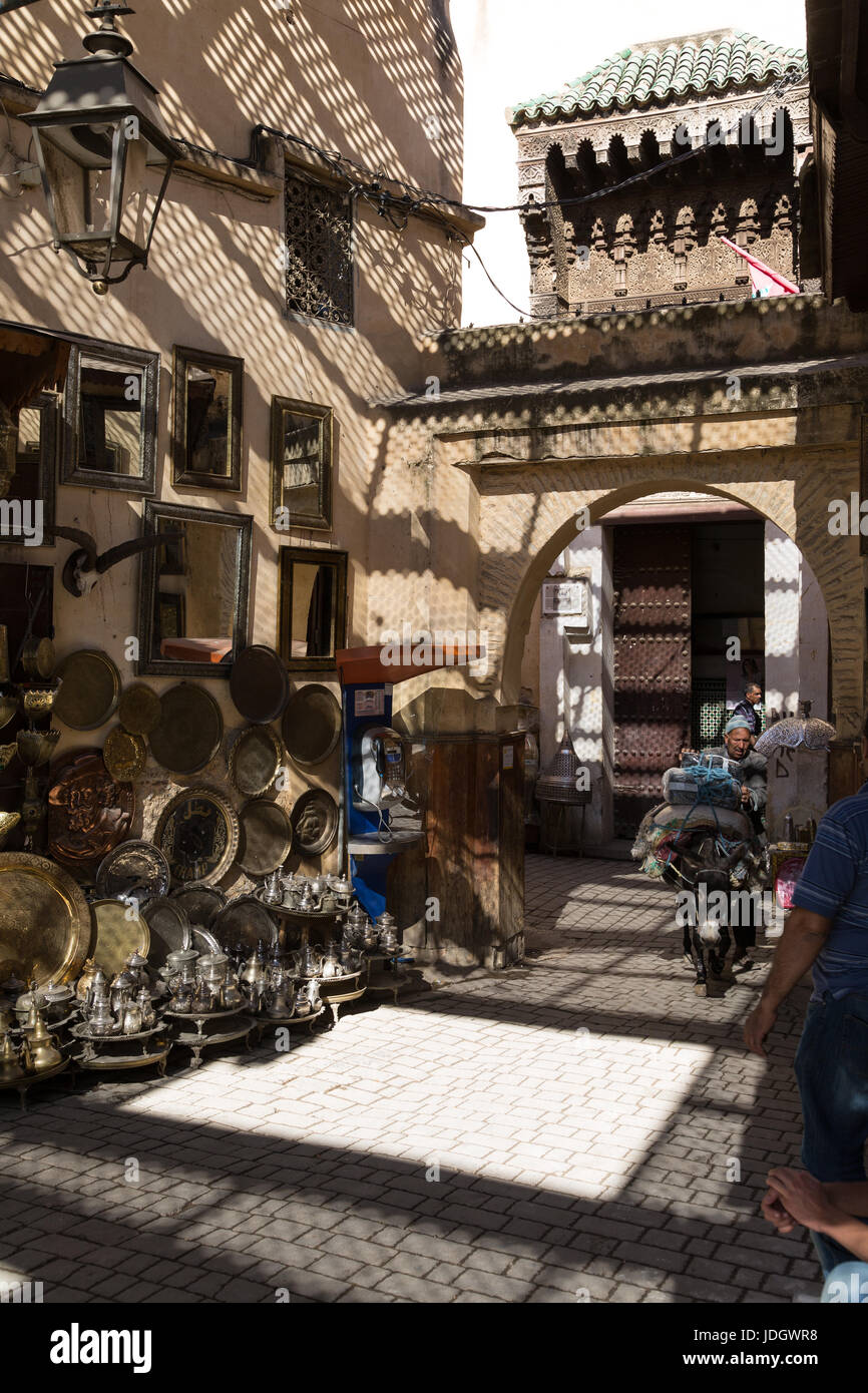 Brass and metal trays, teapots and other fancy goods on the street outside a small shop in Fez, Morocco. A man guides Stock Photo