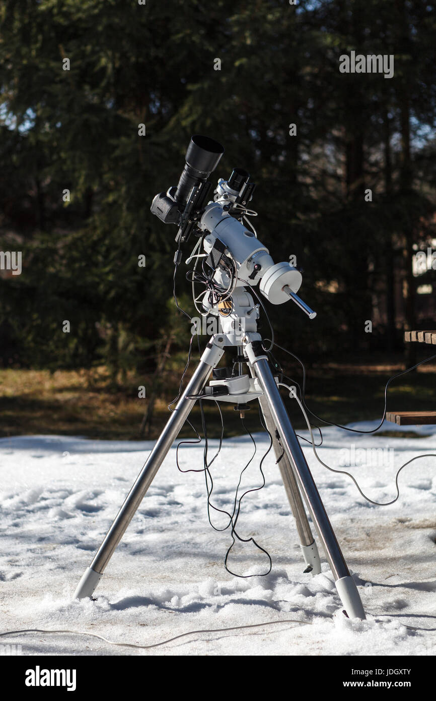 Professional astrophotography setup equipped with DSLR camera, telephoto lens and guider scope ready for night session - Stock Image