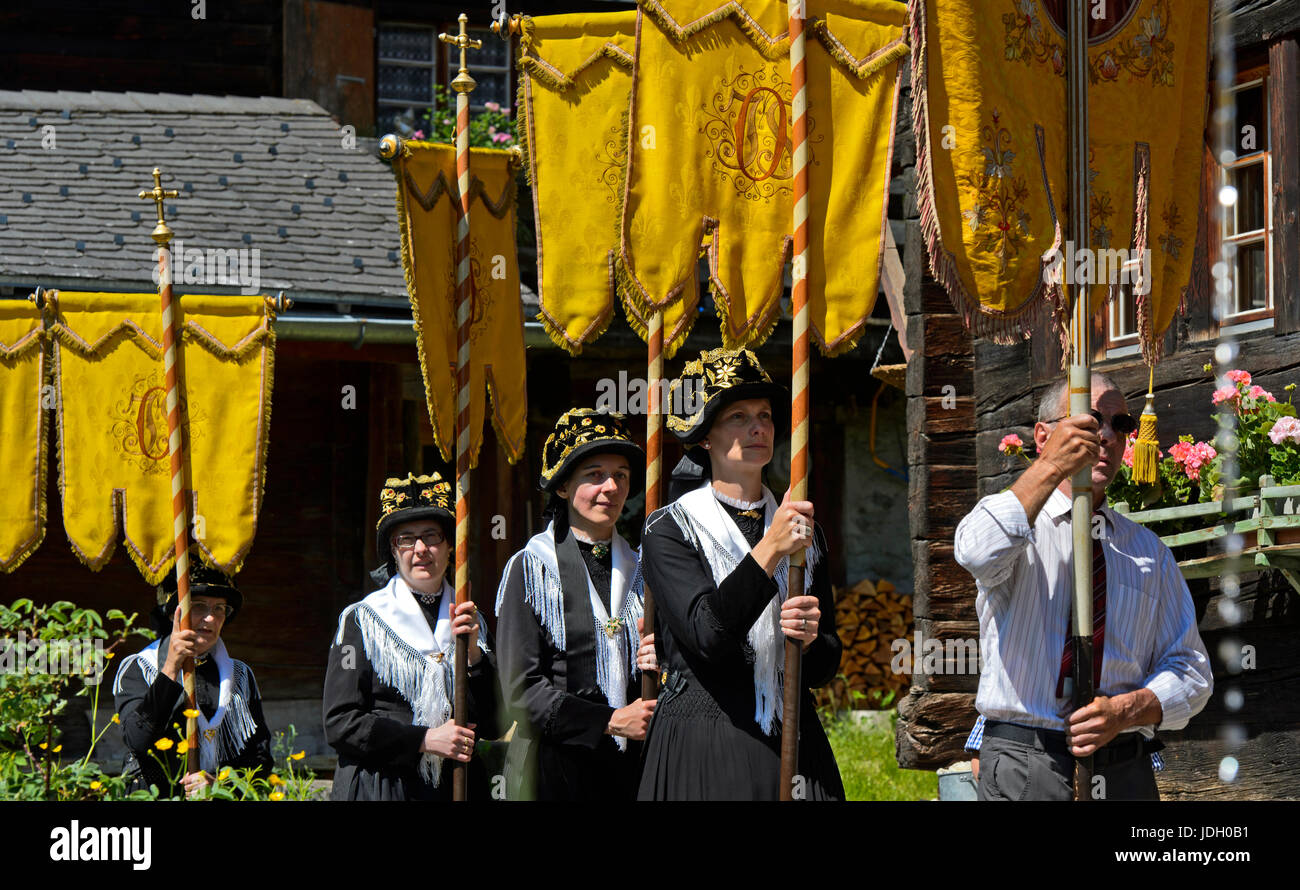 Women in costume carrying religious banners at the Corpus Christi procession, Blatten, Lötschental, Valais, - Stock Image