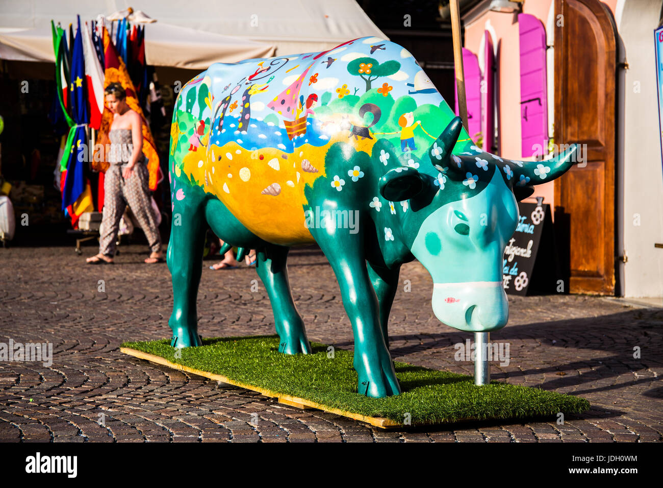 Decorative, human made cow with different colorful drawings in city center - Stock Image