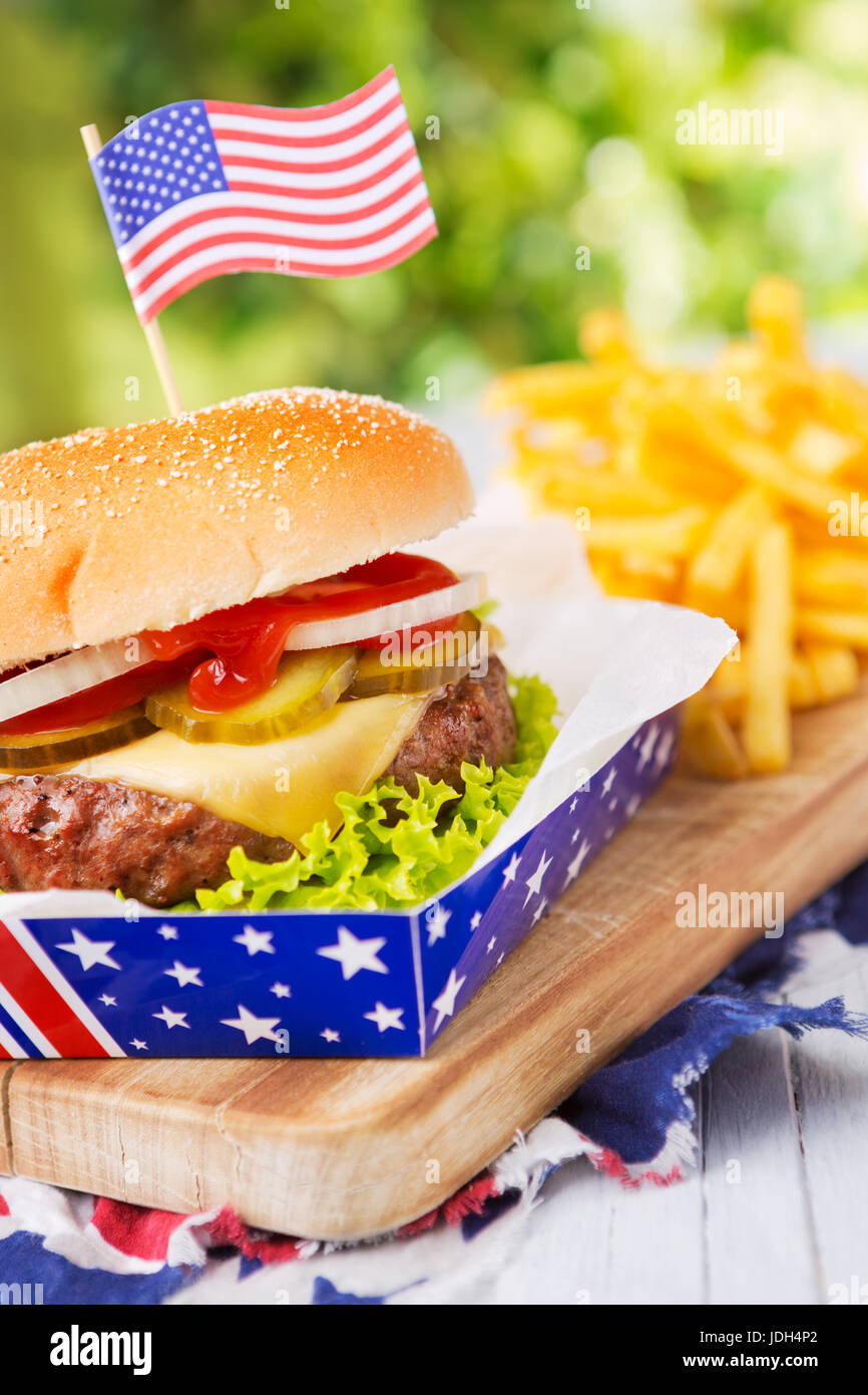 A tasty burger with fries on an outdoor table. - Stock Image