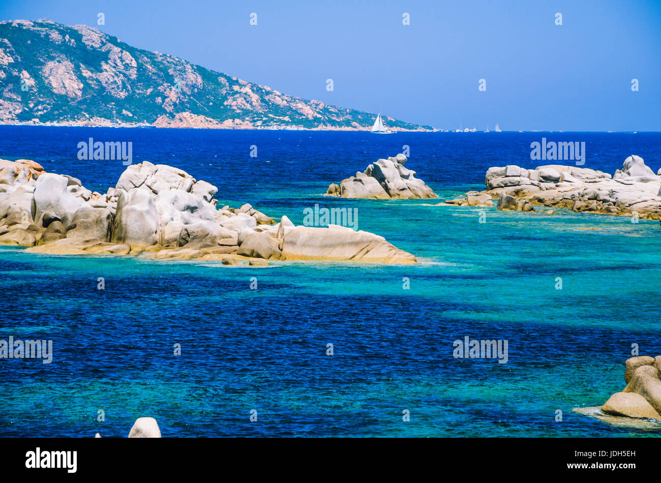 Granite rocks in sea, amazing azure water, white sailboat in background near Porto Pollo, Sardinia, Italy. - Stock Image