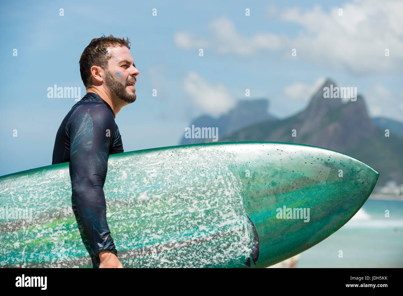 RIO DE JANEIRO - FEBRUARY 10, 2017: Brazilian surfer walks with surfboard along the shore at Arpoador with two brothers - Stock Image