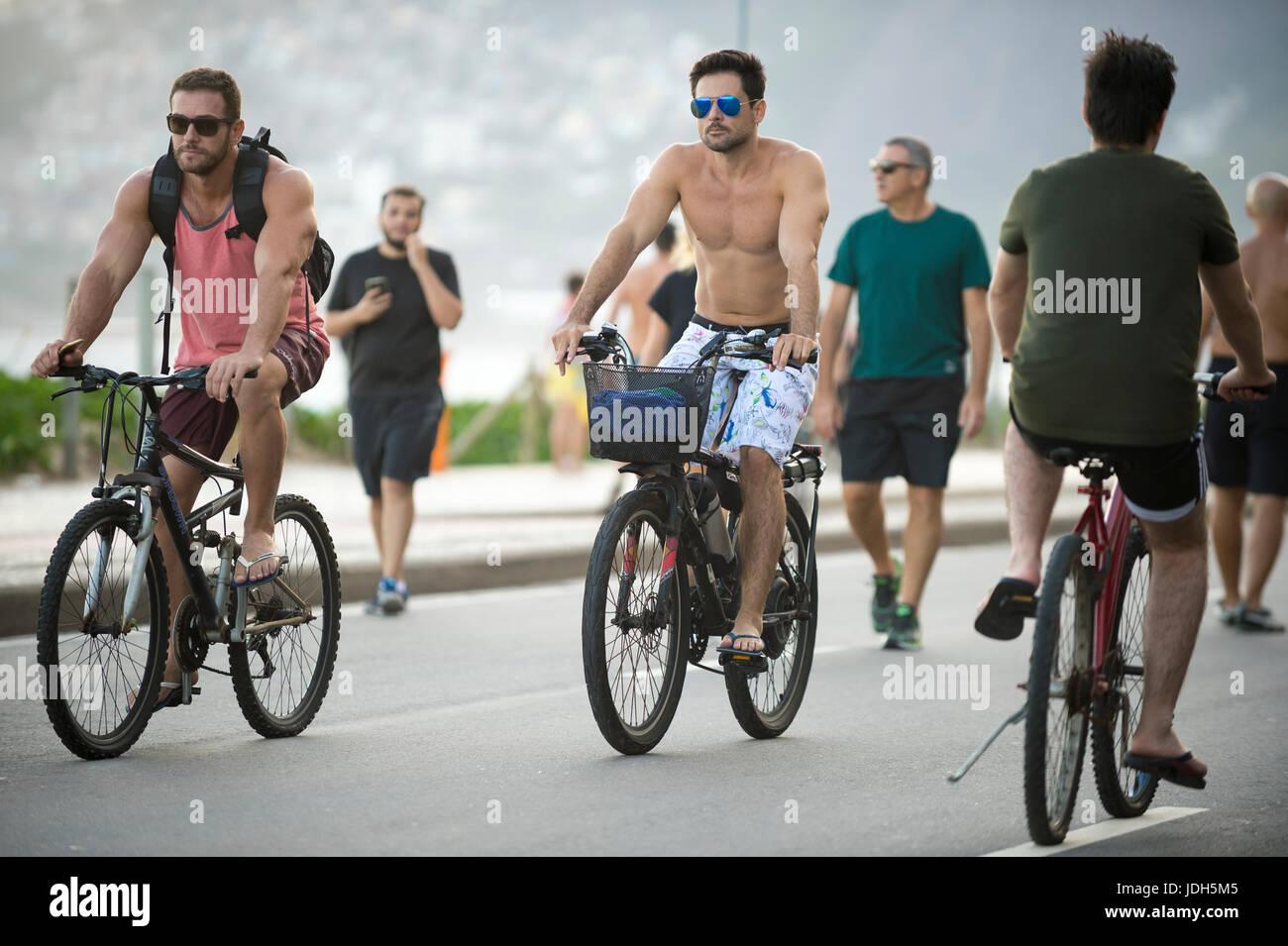 RIO DE JANEIRO - MARCH 26, 2017: Brazilians ride bicycles alongside pedestrians on the Ipanema Beach beachfront - Stock Image