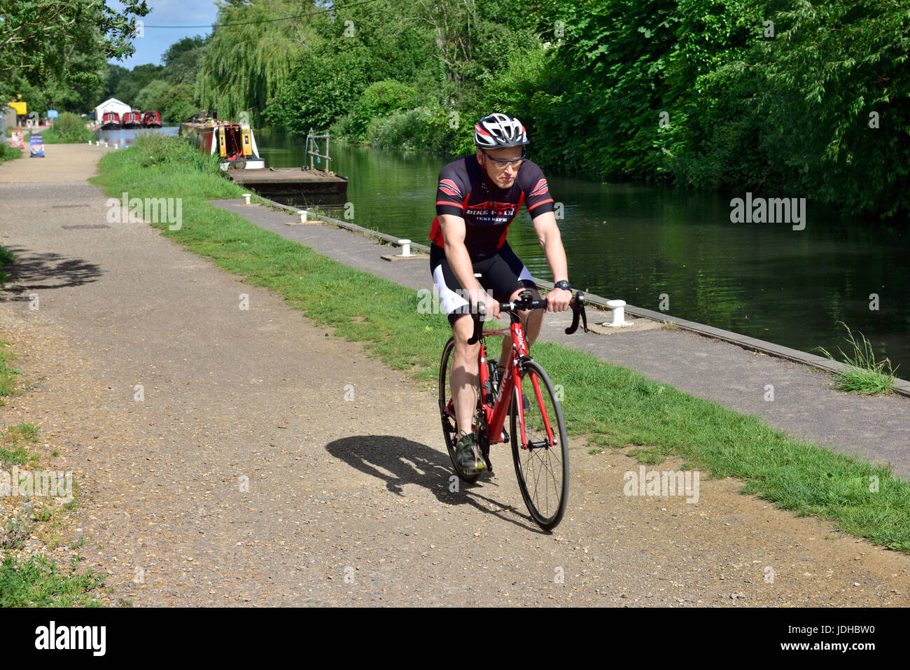 Cyclist on National Cycle Network along towpath of Kennet and Avon Canal near Theale, West Berkshire, UK Stock Photo