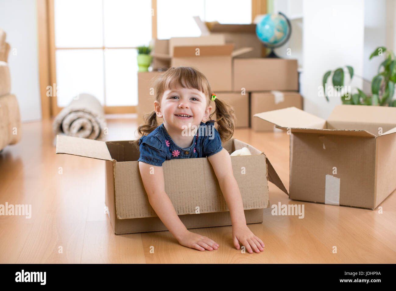 Just moved into a new home. Child into cardboard box. Stock Photo