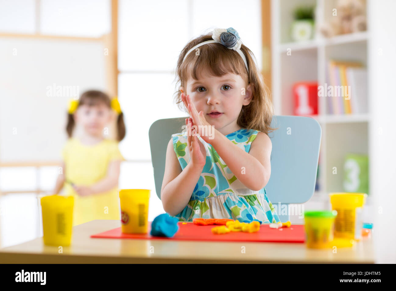 Preschooler girl having fun together with colorful modeling clay at a daycare. Creative kid molding at home. Children - Stock Image