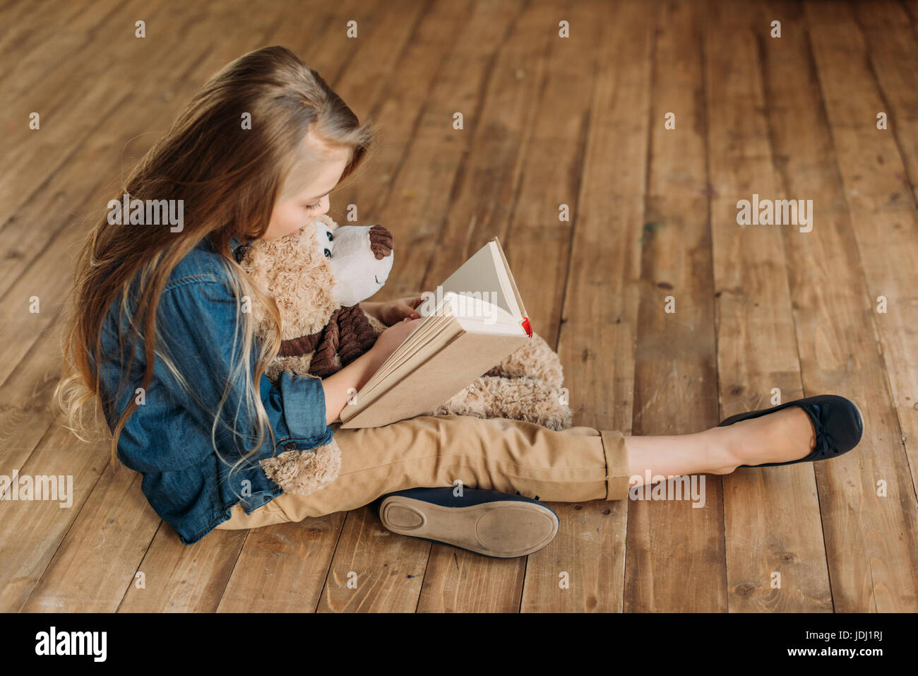 side view of little girl with teddy bear reading book education