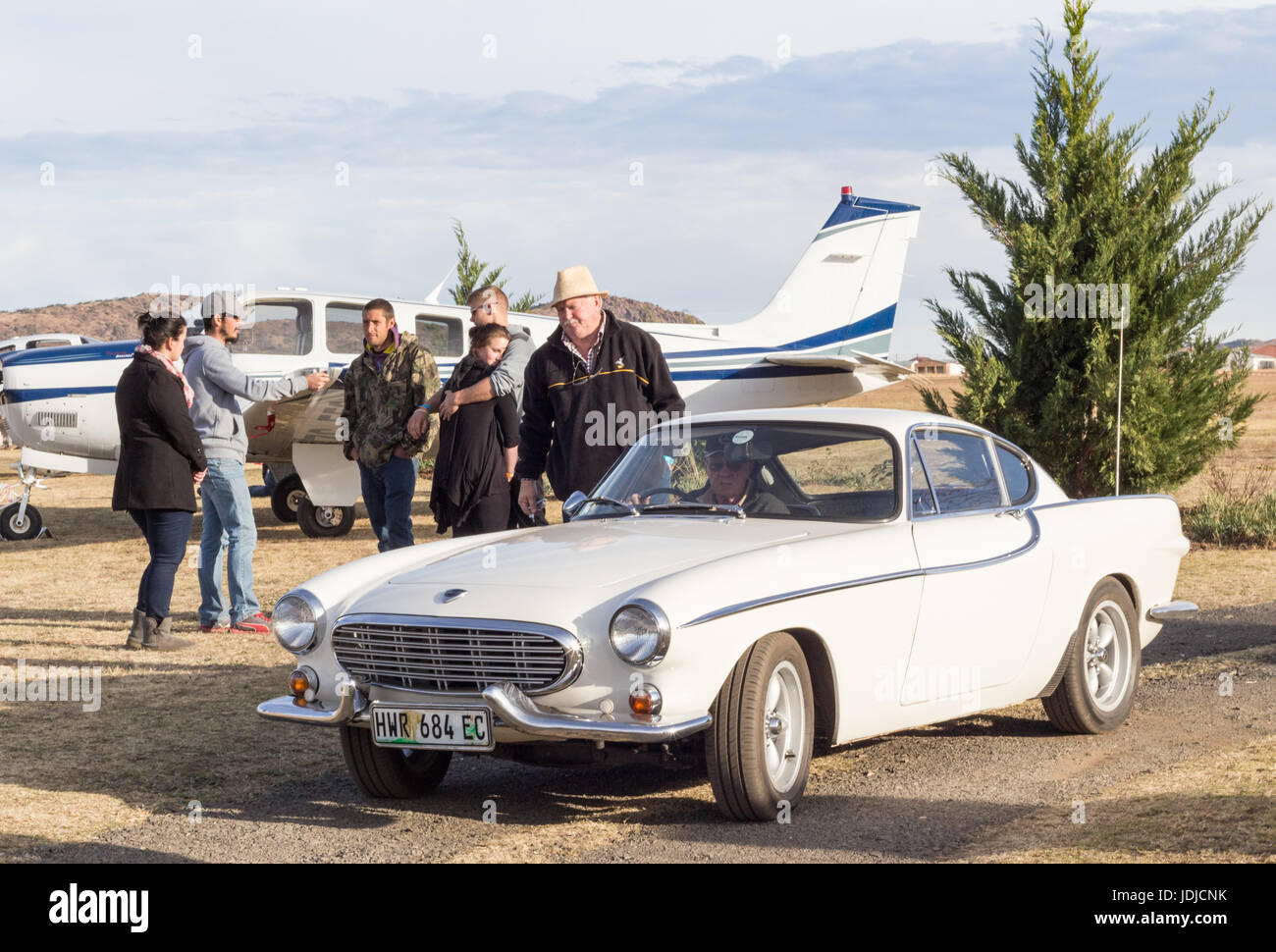 QUEENSTOWN, SOUTH AFRICA - 17 June 2017: Vintage Volvo P1800 car being driven as part of a display at an air exhibition - Stock Image