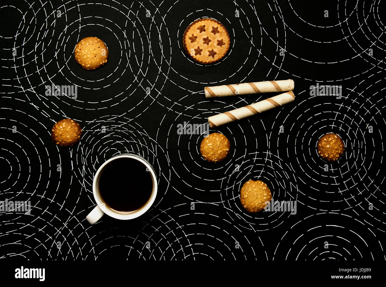 Coffee, sweet biscuits on a black background with concentric circles - Stock Image