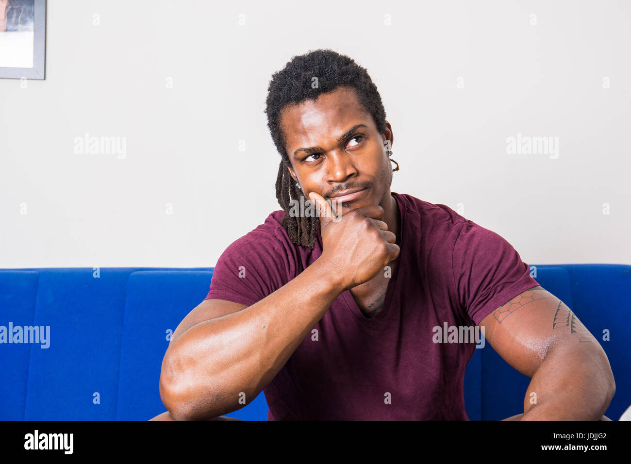 Handsome unsure, doubtful black man thinking, looking up with dubious expression on his face - Stock Image