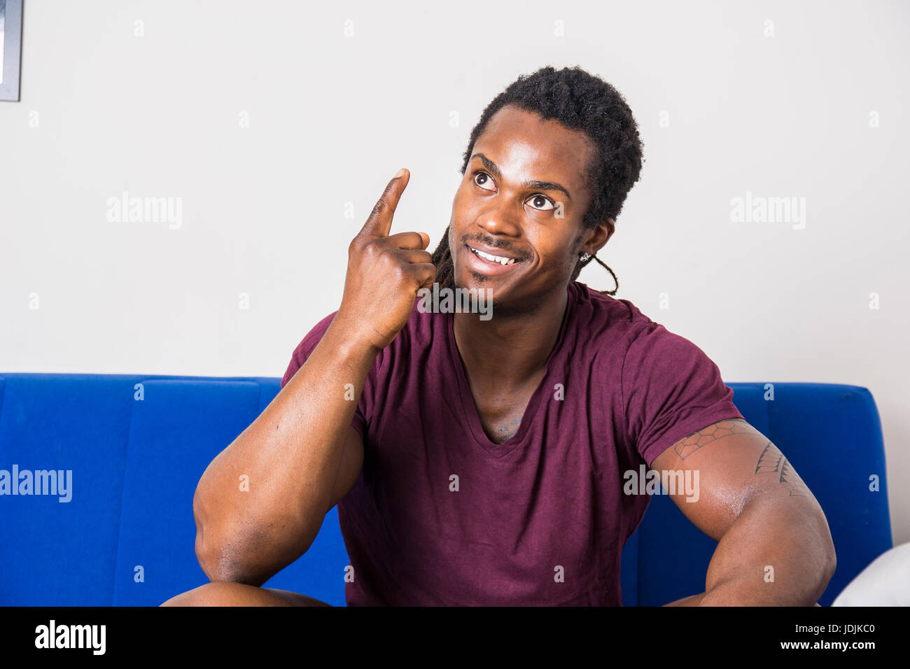 Handsome black young man thinking an idea, doing funny expression and pointing finger up - Stock Image