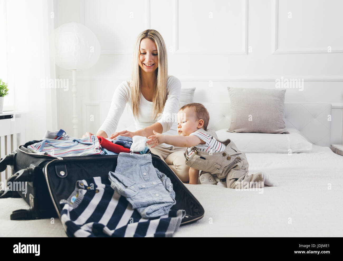 Travelling with kids. Happy mother with her child packing clothes for their holiday - Stock Image