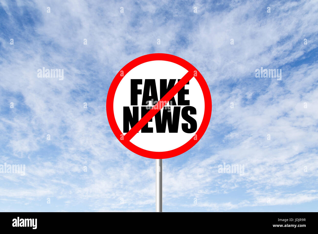 Stop fake news prohibitory traffic sign against blue cloudy sky - Stock Image