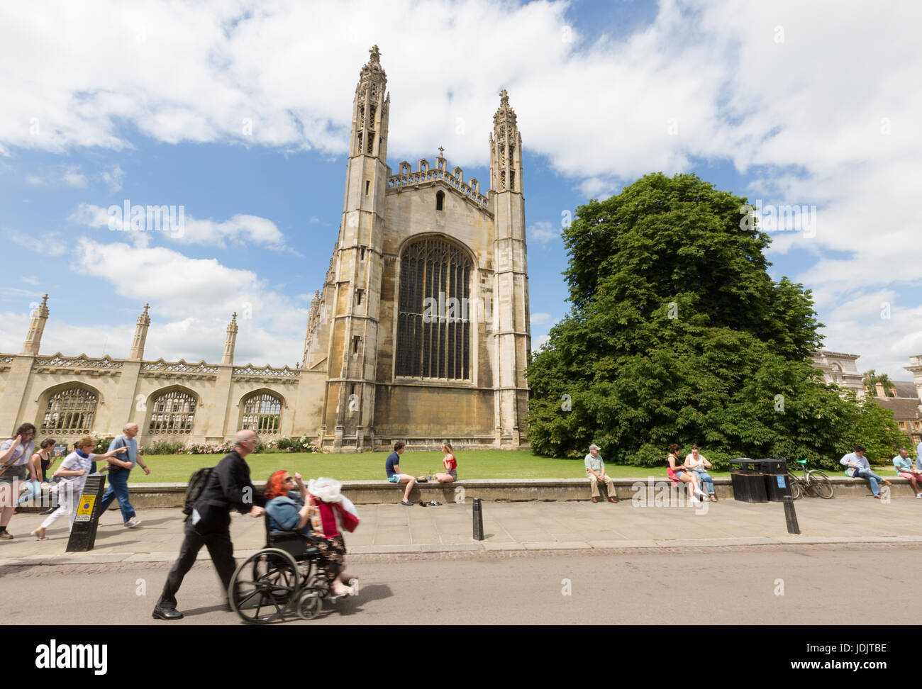A man pushing a disabled woman in a wheelchair past Kings College Chapel, Kings Parade, Cambridge UK - Stock Image